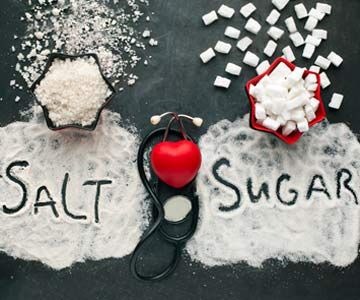 Salt and sugar sprinkled over a table with a stethoscope in-between.