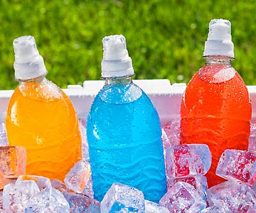 Three colorful sports drinks on ice.
