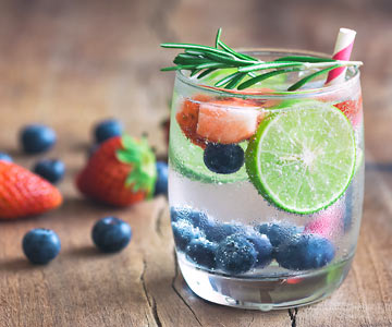 Glass of water with blue berries, strawberries, lime and  sprig of rosemary..