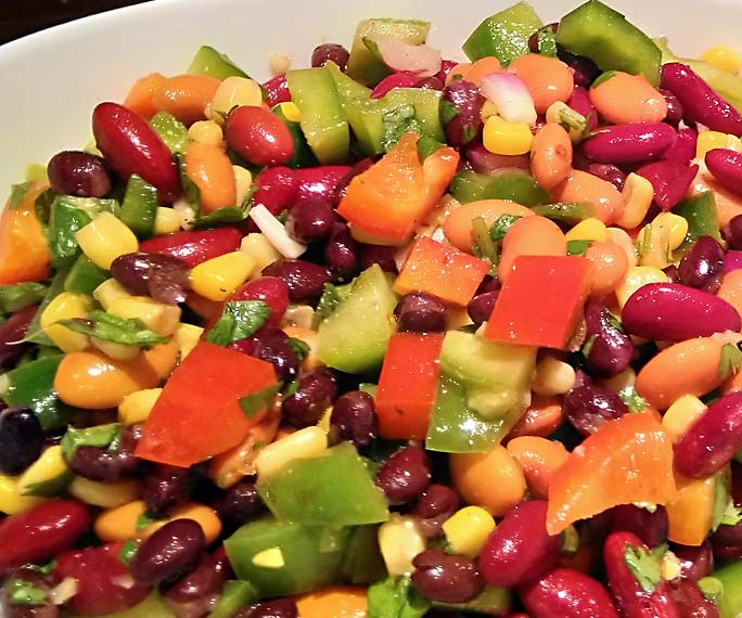 Close up of the ingredients in pepper bean salad: kidney beans, bell peppers, tomatoes, corn.