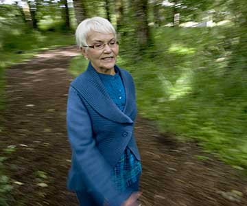 Elderly short and white haired orthopedic patients walks quickly in the forest.