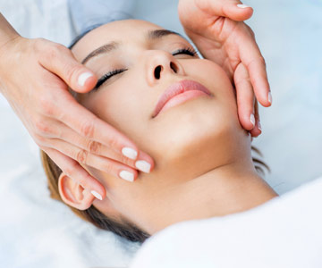 Woman receiving a luxurious facial massage.