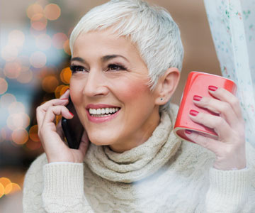 Woman making a call on her phone during the Christmas season.