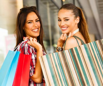 Two women shopping with colorful shopping bags on their shoulders.