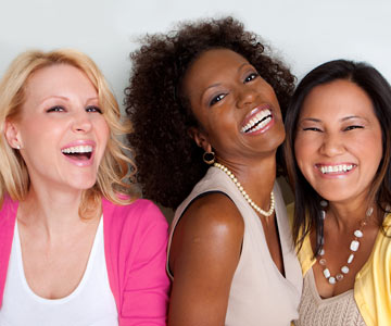 Three women laughing together.