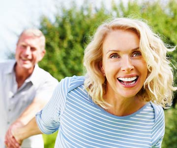 Smiling woman with her husband outdoors.