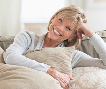 Woman smiling while cozied up on her couch.