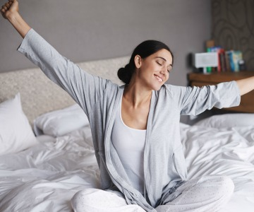 Woman happily stretches after a relaxing night of sleep.
